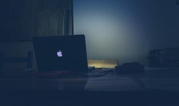 Ordenador en escritorio iluminando con la pantalla la pared de fondo