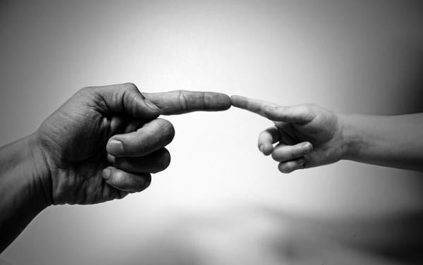 Manos de adulto y niño tocándose con el dedo índice