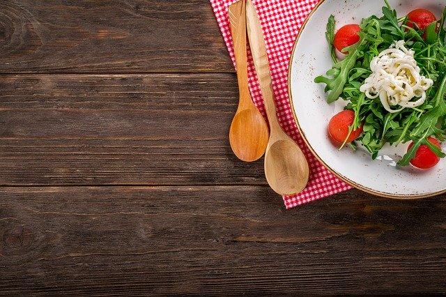 Foto de un plato de rúcula, tomates y queso